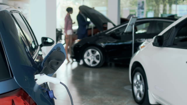 Charging of electric car, people opens the hood of car on blurred background The charging of electric car on the foreground in car dealership. Sexy woman and salesman comes to the automobile on blurred background and opens a hood of car. People are looking on the motor of the modern auto. car salesperson stock videos & royalty-free footage