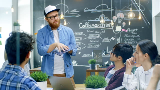 charismatic team leader talks with his team of progressive engineers about renewable energy, he's holding extra efficient prototype of the solar panel. talented young people stylish office environment. - efficacia video stock e b–roll