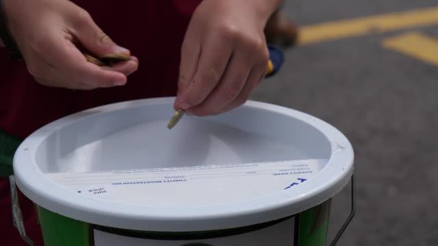 Bидео Charity cash donation box or bucket close up