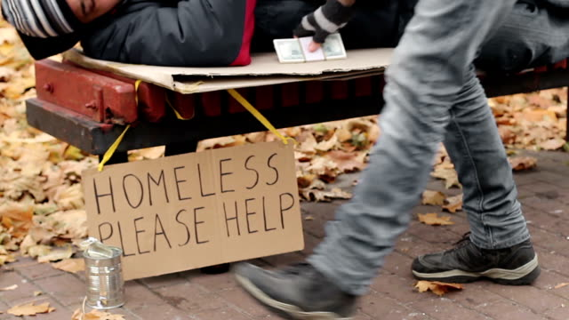 Charity, kind man leaving pack of money on bench while homeless male sleeps video
