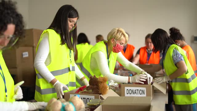Charity organisation  Collecting Food Donations In Warehouse in Time of Pandemic Female volunteers with protective face masks collecting food for donation in a warehouse giving tuesday stock videos & royalty-free footage