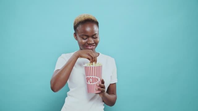 vídeos de stock, filmes e b-roll de menina americana afro encantadora que come a pipoca do balde - balde pipoca