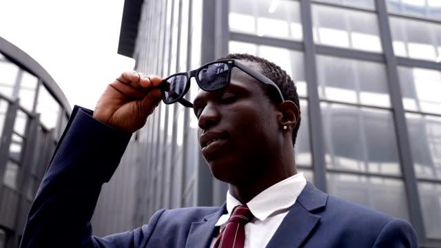 vídeos de stock, filmes e b-roll de homem de negócios preto confiante e encantador tira seus óculos escuros - moda urbana