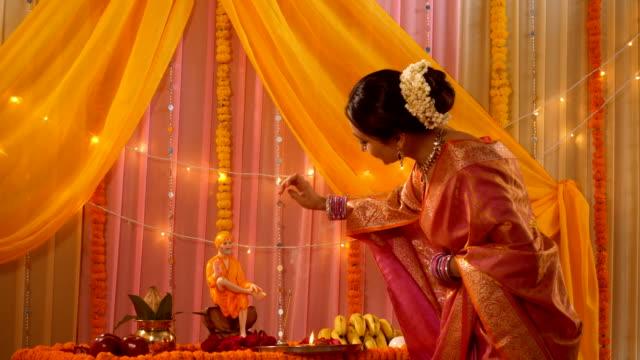 charming and smiling indian woman in traditional dress putting tilak on sai baba idol (sai pujan) - sari filmów i materiałów b-roll