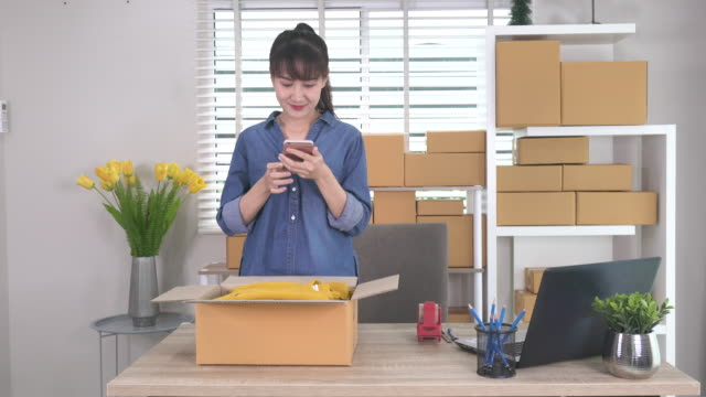 vídeos de stock, filmes e b-roll de mulher de negócio asiática bonita encantadora do proprietário do adolescente que toma a foto às camisas com telefone de pilha ou câmera digital do smartphone para o borne para vender em linha no conceito do estilo de vida do empreendedor do internet - fotografia arte e artesanato