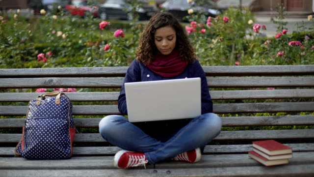 charming biracial woman sitting on bench outdoors, working on laptop, freelancer - bench stock videos & royalty-free footage