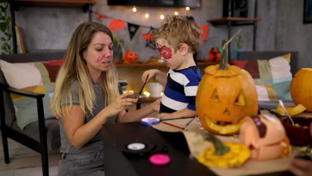 Charming boy using brush to paint his mother face for a Halloween night Playful mother and her son using a face paint to apply on their faces so they can prepare their costumes for Halloween night after they finished with pumpkin carving in their home halloween covid stock videos & royalty-free footage