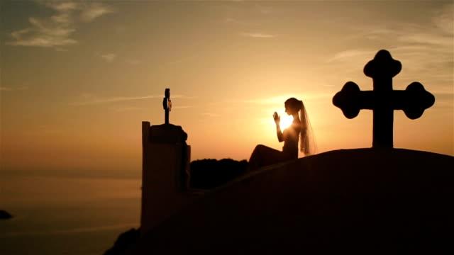 splendida sposa prega alla croce blu cielo al tramonto sfondo - isole egee video stock e b–roll