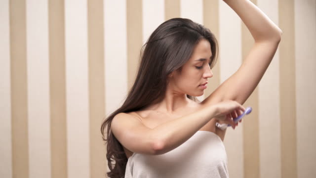 A charming brown-haired woman holds a razor in right hand and starts shaving her left armpit, then she changes hands video
