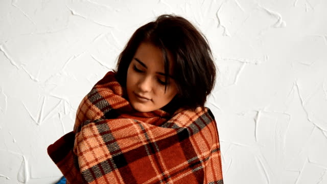 charming brunette stands near a wall and wrapped in a warm blanket video