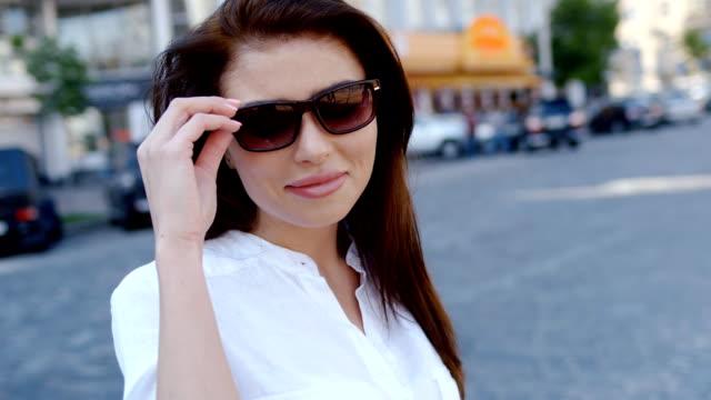 Charmante femme brune en chemise blanche, mettre des lunettes de soleil sur son statut de cheveux longs en bonne santé de rue moderne animée - Vidéo