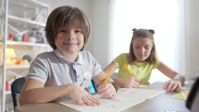Charming Caucasian boy looking at camera and smiling with blurred girl drawing at background. Portrait of cute confident schoolboy posing in school with classmate. Lifestyle and education.