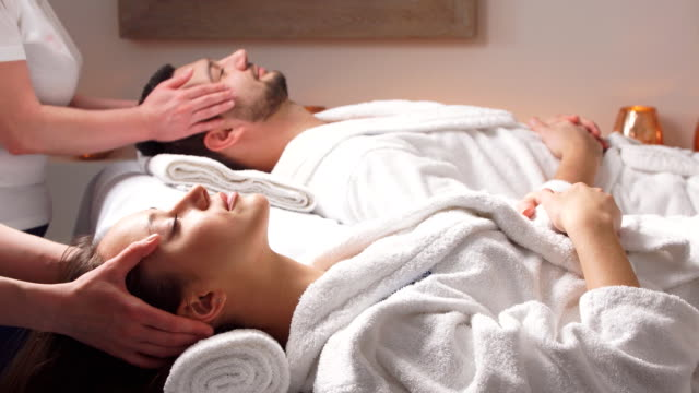 charming couple enjoying a head massage in modern wellness salon - viziarsi video stock e b–roll