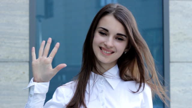 charming girl smiles at the camera and shows gesture five video