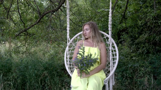 Charming girl with a bouquet of blue wildflowers sitting on a swing in a yellow dress in nature on a sunny day. She straightens her hair and poses for the camera. Fashion portrait. Close-up. 4K.