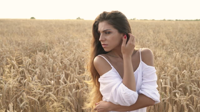 Charming lady walking in wheat field at sunset. Woman is dreamily looking at the sides and waiting for somebody. True emotions