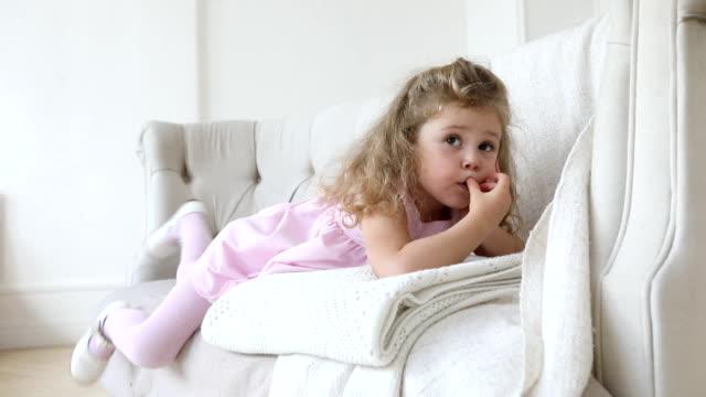 ソファーでポーズをとって魅力的な少女 - チャームポイント点の映像素材/bロール