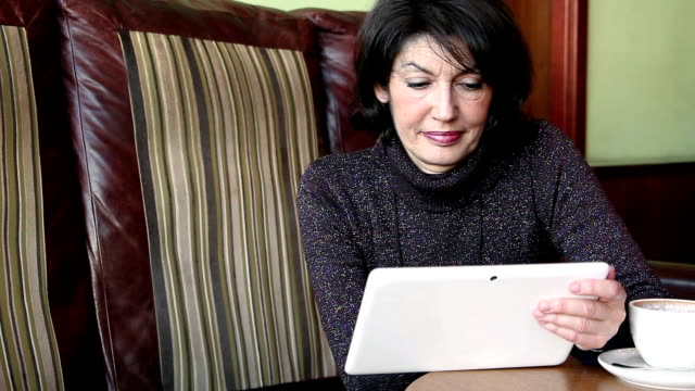 Charming mature woman  with digital tablet Charming mature black haired  woman sitting in the cafe  and using a with digital tablet . charming stock videos & royalty-free footage