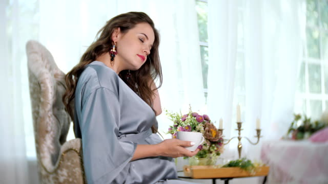 Charming pregnant woman with cup of tea