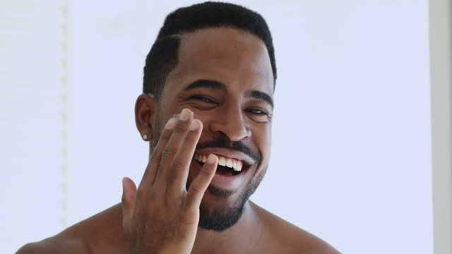 Charming smiling african guy applying facial cream looking at camera Charming smiling afro american guy applying facial cream on cheek looking at camera. Happy shirtless bearded african man putting creme on face for dry oily skin care beauty concept. Close up portrait. body care stock videos & royalty-free footage
