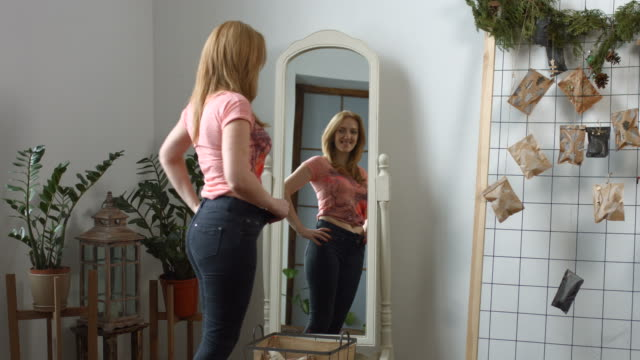 charming woman admiring her body after weight loss - jeans video stock e b–roll