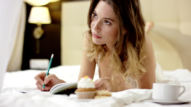 vídeos de stock e filmes b-roll de charming woman dressed in sleepwear is writing something down her notebook with cup of coffee and cupcake - liga desportiva