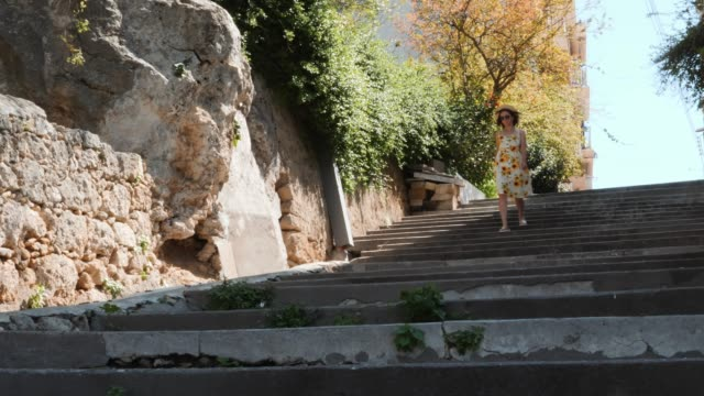 Charming woman in summer yellow dress walking down concrete staircase, holding hat with her hand and spinning in place
