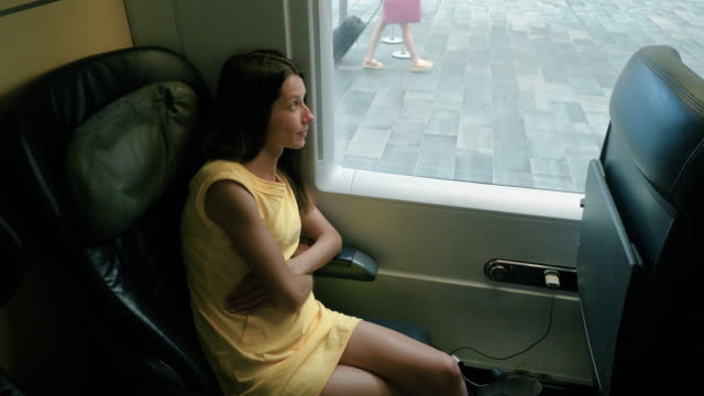 Charming woman looking through window while travelling in train to Madrid. 4K