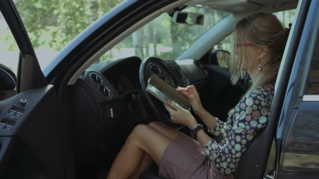 charmante frau, die vernetzung mit tablet-pc im auto - tablet mit displayinhalt stock-videos und b-roll-filmmaterial