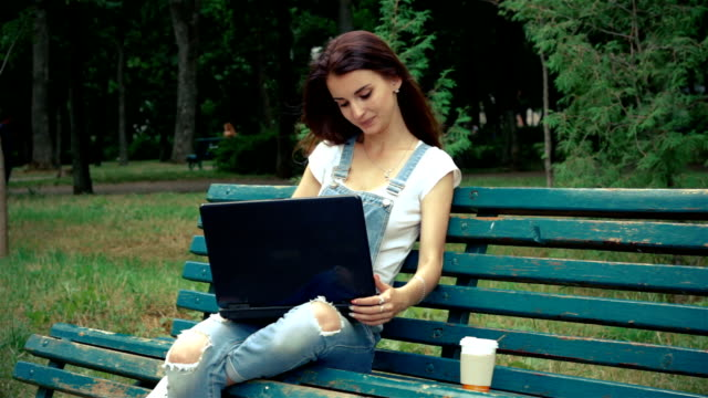 charming woman sits on the street and on prints laptop video