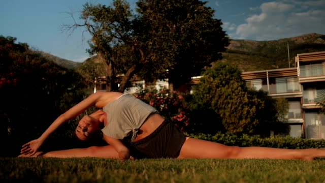 Charming woman sitting on a twine stretches her hands on grass video