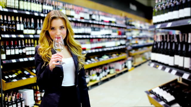 Charming woman tasting a white wine in the wine shop video
