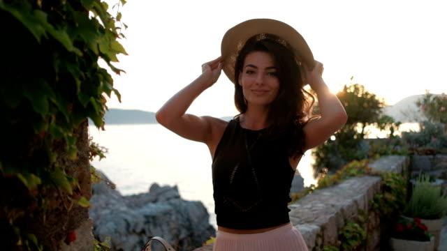 Mujer encantadora lleva sombrero de ala ancha en la costa rocosa - vídeo