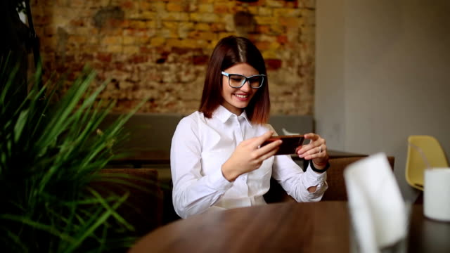 Charming woman with beautiful smile reading good news on mobile phone during rest in coffee shop, happy Caucasian female watching her photo on cell telephone while relaxing in cafe during free time video