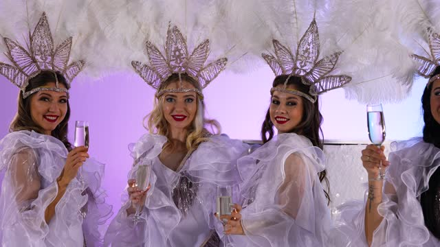 vídeos de stock e filmes b-roll de charming women in white dance costumes posing with glasses of champagne. dancers in the image of the snow queens with feather headdresses on the background of a light studio. close up. slow motion - bolo rainha