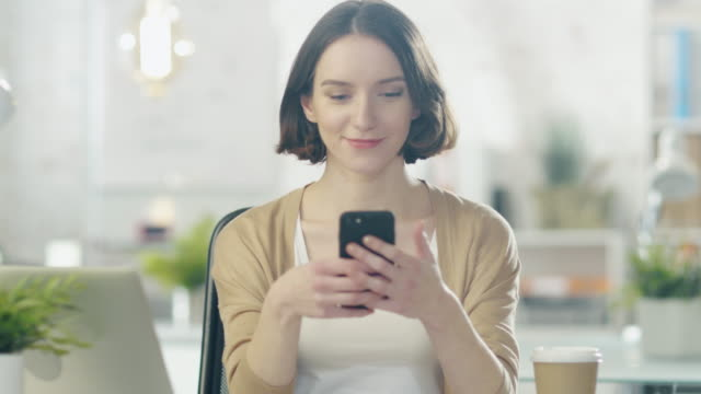 Charming Young Creative Woman Sits at Her Desk in a Bright Office ant Uses Smartphone.