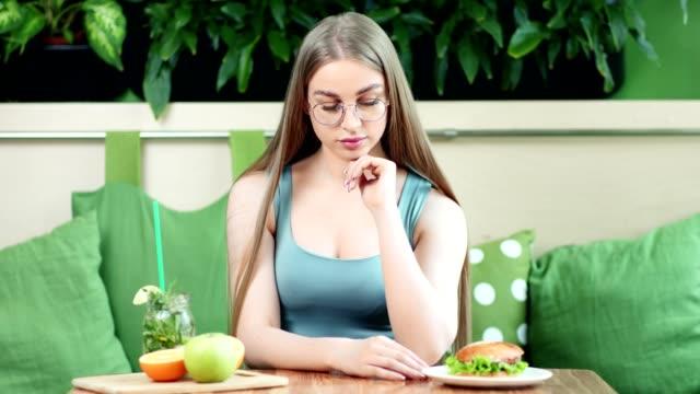 魅力的な若いフィットネスの女の子は、新鮮な健康フルーツ飲料と不健康ハンバーガーの間で選択 - ローフード点の映像素材/bロール