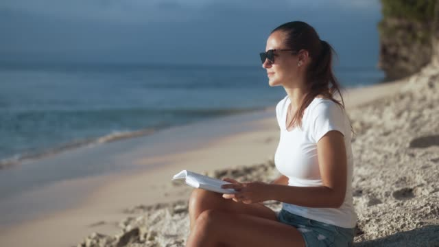 Charming young girl reads a book while sitting on a sandy shore