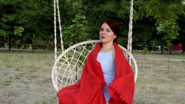 A charming young girl with red hair sits and poses for the camera on a swing in the park at the sunset of a summer day. She covers herself with a red blanket and smiles sweetly. Close-up. 4K.