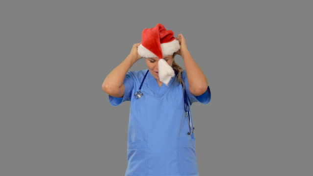 Charming young nurse dancing on grey screen