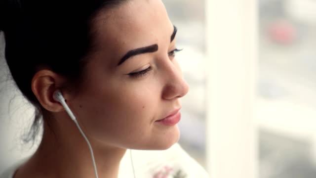 musik dinleme pencere oturan kulaklıklar çekici genç kadın - kulak i̇çi kulaklık stok videoları ve detay görüntü çekimi