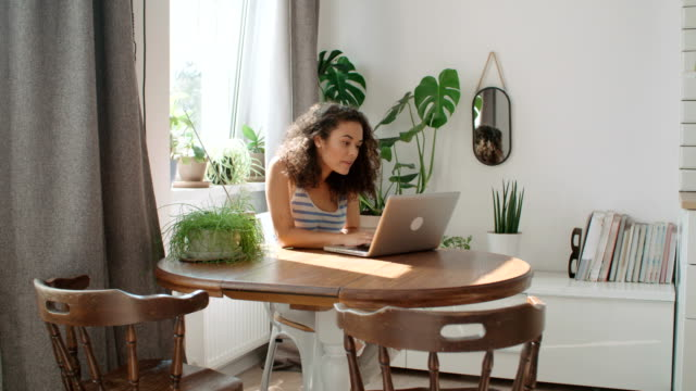 Charming young woman typing on laptop computer in a kitchen.