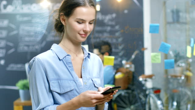 Charming Young Woman Uses Smartphone While Standing in the Busy Creative Office with Stylish Talented People. Charming Young Woman Uses Smartphone While Standing in the Busy Creative Office with Stylish Talented People. charming stock videos & royalty-free footage