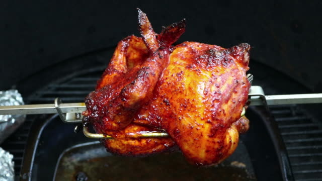 Charred rotisserie chicken over open flames in a barbecue. video