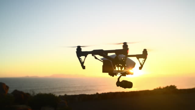Chasing adventure 4k video footage of a person operating a drone outside camera photographic equipment stock videos & royalty-free footage