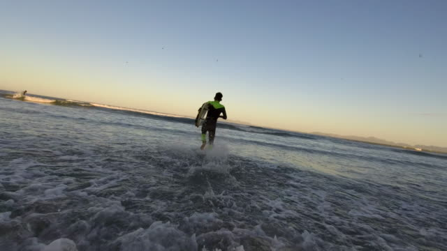 Chasing the early morning waves A young black male surfer runs with his board into the surf ready to catch some early morning waves western cape province stock videos & royalty-free footage