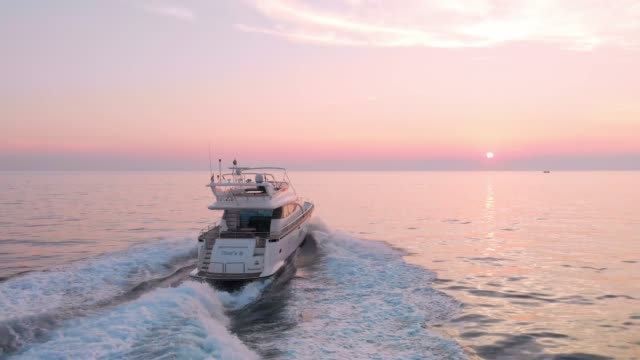 Chasing the sunset - Luxury yacht Aerial view of a luxury yacht on the sea at sunset. Perfect unobstructed view over the horizon from this spot. Handsome man the owner of the yacht living the good life. yacht stock videos & royalty-free footage