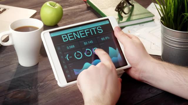 Checking benefits records using digital tablet at desk