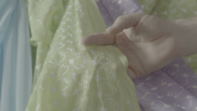 Checking Fabric BAHRAIN - CIRCA 2012: A hand is checking a swatch of fabric in an Arab souk or market place. sari stock videos & royalty-free footage