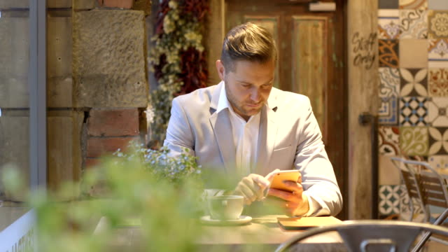 Checking his mobile on a coffee break video